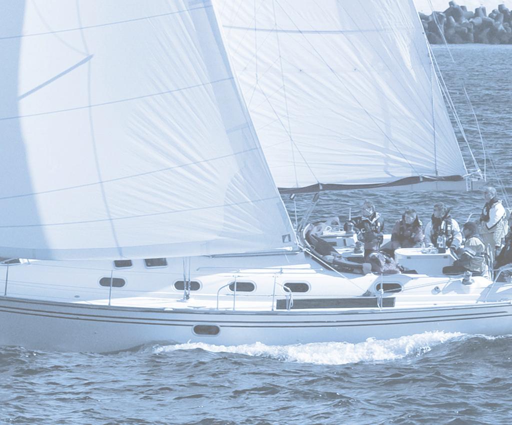 Segelboot mit weißen Segeln und 6 Mann Besatzung segelt durch das Wasser